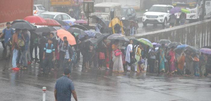 People were seen waiting for buses during heavy rain at General Thimayya Circle in Madikeri on Wednesday.