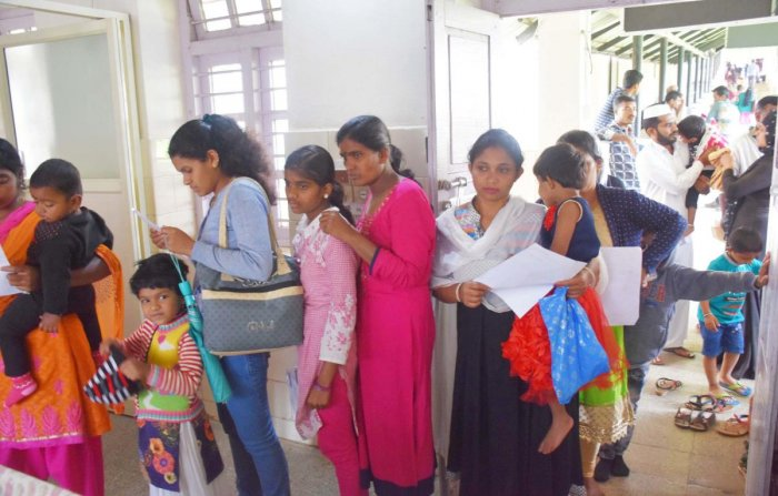 Parents wait with their children in a queue at District Children's Hospital in Madikeri.