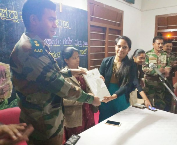 Deputy Commissioner Annies Kanmani Joy presents a certificate to a soldier in Kodagu on Tuesday. SP Dr Suman D Pennekar and ZP CEO K Lakshmi Priya are also seen.
