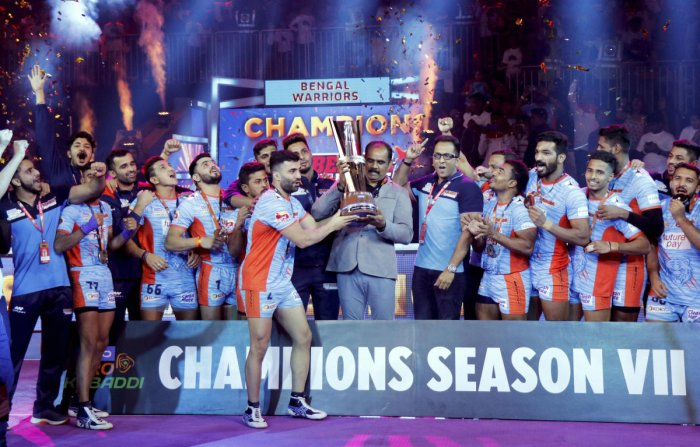 Players and officials of Bengal Warriors celebrate with the trophy after defeating Delhi Dabbang KC during the finals of the seventh edition of Pro-Kabaddi league, in Ahmedabad, Saturday, Oct. 19, 2019. Bengal Warriors beat Dabang Delhi 39-34. (PTI Photo)