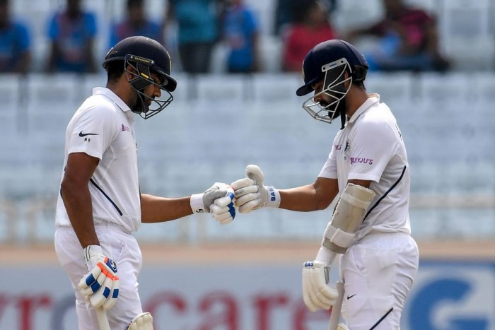 India's Rohit Sharma (L) and teammate Ajinkya Rahane (R) touch gloves during the second day of the third and final Test match between India and South Africa at the Jharkhand State Cricket Association (JSCA) stadium in Ranchi on October 20, 2019. (Photo by AFP)