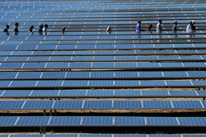 People walk between solar panels during the inauguration of a solar farm in Giuncaggio. (AF Photo)