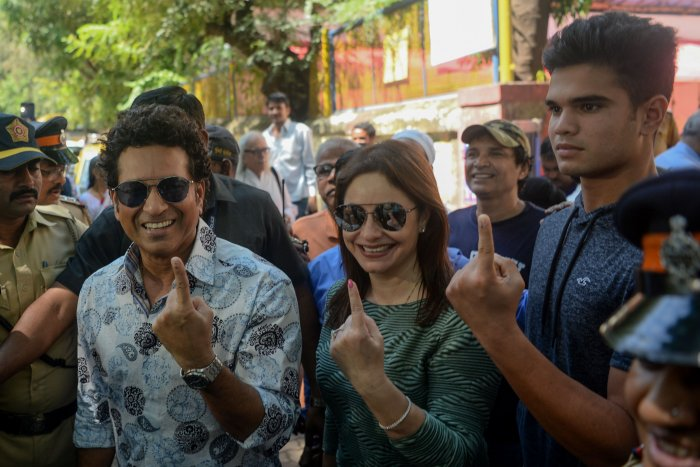 Former cricketer and captain Sachin Tendulkar (L) shows his inked finger after casting his vote along with his wife Anjali Tendulkar (C) and his son Arjun Tendulkar (R) during the state assembly election in Mumbai. (AFP Photo)