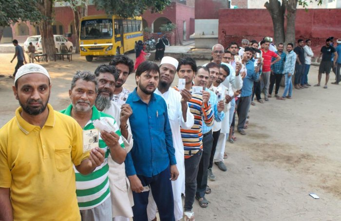 Voters stand in a queue and show their voting cards as they wait to cast their votes at a polling station for the Haryana Assembly elections, at Badkal in Faridabad, Monday, Oct. 21, 2019. (PTI Photo)