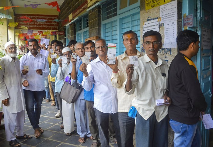 Voters stand in a queue and show their voting cards as they wait to cast their votes at a polling station for the Maharashtra Assembly elections. (PTI Photo)
