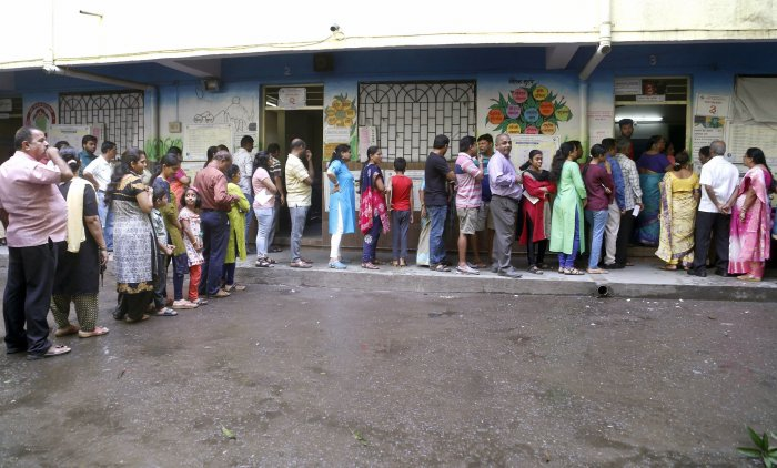 Voters stand in a queue displaying their voter card outside a polling station during Maharashtra Assembly elections, in Thane. (PTI Photo)