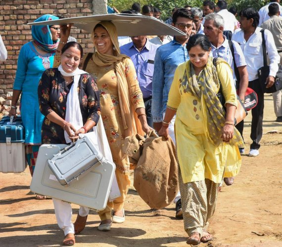 Polling officials, carrying the Electronic Voting Machine (EVMs) and other necessary inputs, leave for their poll duty, on the eve of Haryana Assembly elections, in Sonipat, Sunday, Oct. 20, 2019. (PIB/PTI Photo)