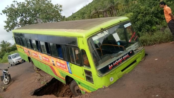 An NWKRTC bus stuck in a trench after road caved in due to heavy rain, near Chikkadinni village in Hukkeri talukof Belagavi district.