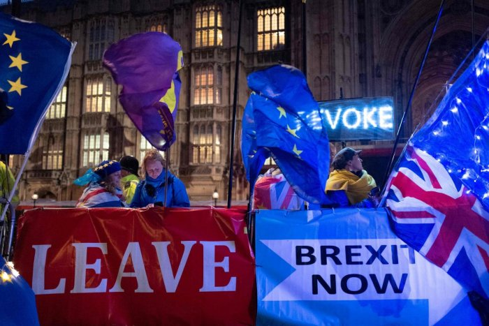 Pro and anti-Brexit aprotesters wave flags and hold banners as they demonstrate outside of the Houses of Parliament in central London. (AFP Photo)