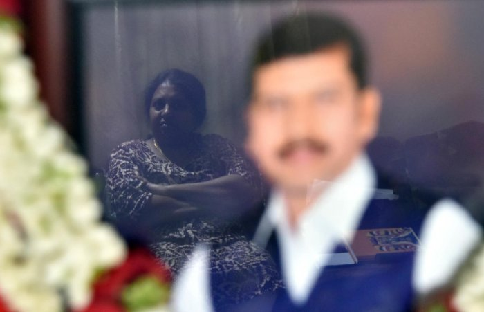 Dr Pavana Dibbur (reflected in glass), wife of Dr Dore, has never stepped into a police station. She hopes justice will be quick. DH Photos by Janardhan B K