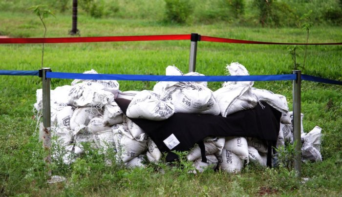 Explosives found in a bucket are kept at an isolated place, covered by sand bags, at the railway station premises in Hubballi.