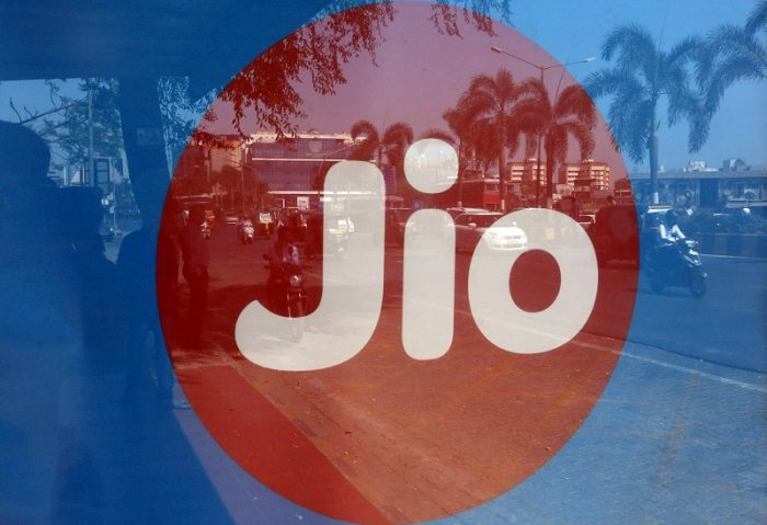 Commuters' reflections are seen on an advertisement for Reliance Industries' Jio telecoms business at a bus stop in Mumbai. (Reuters Photo)