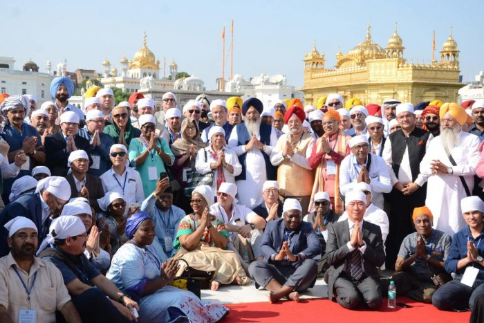 Minister of State for Civil Aviation Hardeep Singh Puri (centre with red turban) poses for a picture with diplomats and ambassadors of 91 countries as they pay their respects at the Golden temple in Amritsar on October 22, 2019. (Photo by NARINDER NANU / AFP)