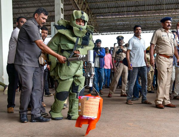 A bomb disposal squad personnel carries a bucket, which contained a parcel allegedly triggering a minor blast, to a safer place, at Hubballi railway station on October 21, 2019. (PTI Photo)