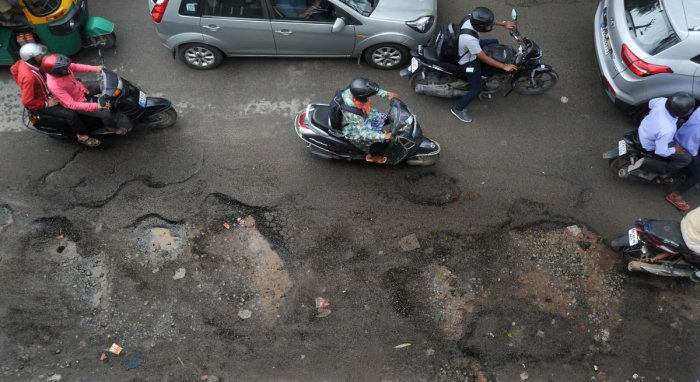 Following heavy rains, several roads in the city are pothole-ridden. Pictured: Commuters try to avoid puddle filled pothole stretch on the busy Kodichikkanahalli Road, Bilekahalli in Bengaluru on Tuesday. | DH Photo: Pushkar V