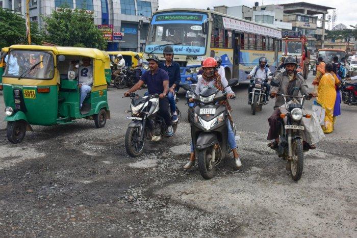 Potholes on Mysuru Road at Nayandahalli Circle (left) and near Bapuji Nagar Cross (above). DH PHOTOs/IRSHAD MAHAMMAD