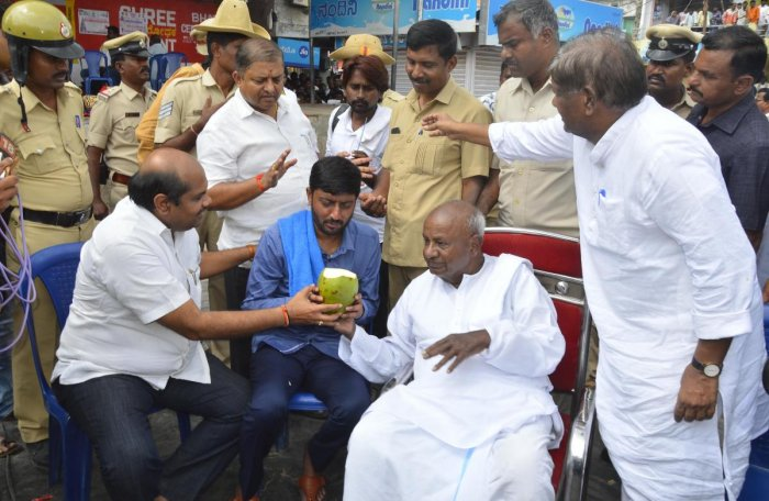 JD(S) national president H D Deve Gowda offers tender coconut to party youth wing leader Sharanagouda Kandakur, who ended his hunger strike, in Yadgir on Wednesday.