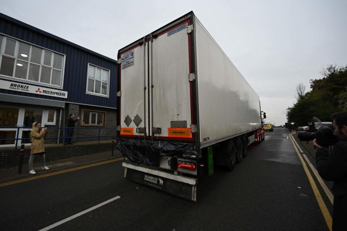 Police officers drive away a lorry, with black plastic visible at the rear, in which 39 dead bodies were discovered sparking a murder investigation at Waterglade Industrial Park in Grays, east of London, on October 23, 2019. AFP