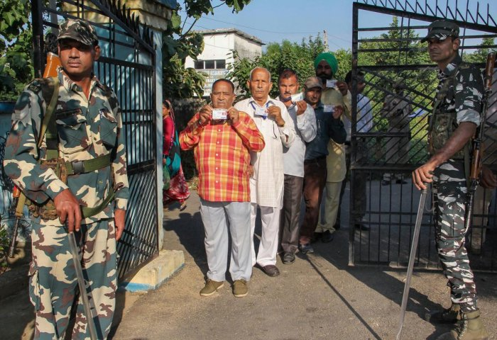 Security personnel stand guard as panchs and sarpanchs queue up to cast their votes for Block Development Committees (BDC) elections in Kashmir (PTI Photo)