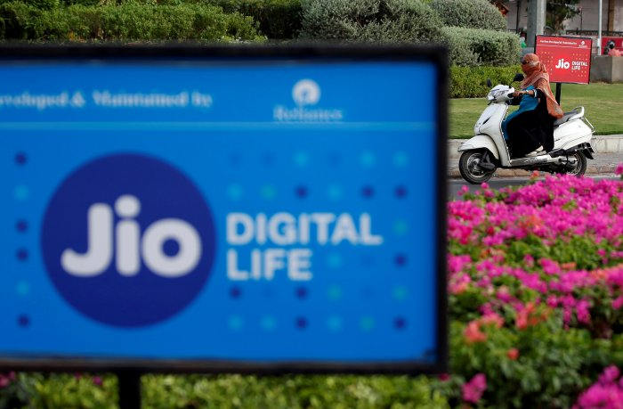 A woman rides her scooter past advertisements of Reliance Industries' Jio telecoms unit, in Ahmedabad. (Reuters Photo)