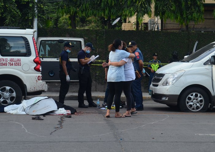 Relatives (R) of slain Clarin town mayor David Navarro mourn next to his body after he and his police escort were ambushed in Cebu. (AFP Photo)