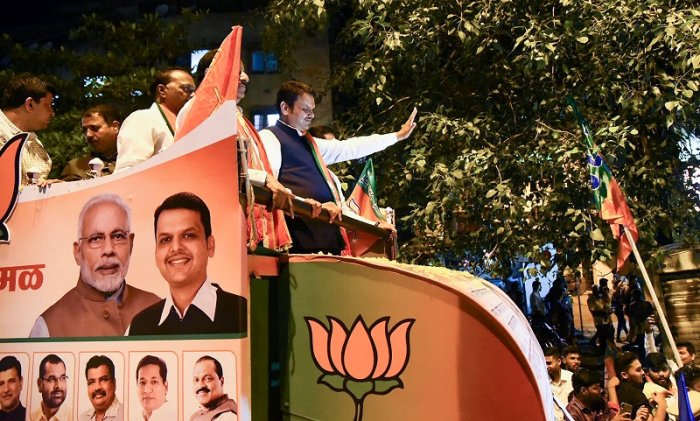 Maharashtra Chief Minister Devendra Fadnavis waves at supporters during a roadshow for BJP candidates for Maharashtra Assembly elections. (PTI Photo)