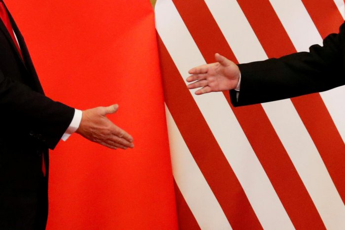 US President Donald Trump and China's President Xi Jinping shake hands. (Photo by Reuters)