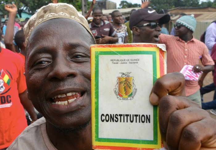 A man holds a copy of Guinea's Constitution as he takes part in a protest against the third term of the Guinean President. (Photo AFP)