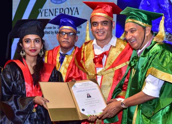 Deputy Chief Minister Dr C N Ashwath Narayan and Yenepoya (Deemed to be University) Chancellor Y Abdulla Kunhi present the gold medal award to best outgoing student Akshatha Chatra, during the ninth convocation, on the university campus in Deralakatte on Friday.