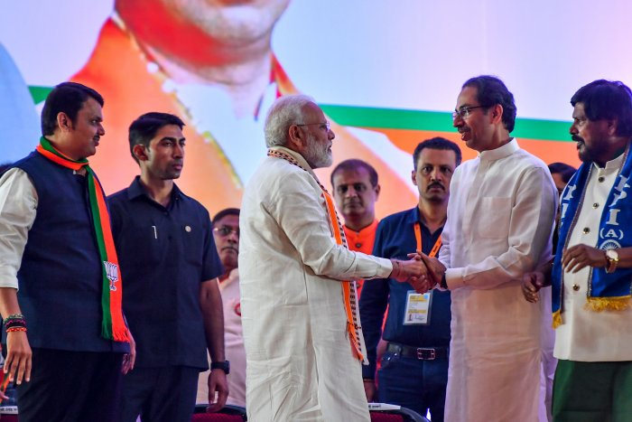 India's Prime Minister Narendra Modi (C) shakes hands with Hindu right-wing party Shiv Sena Chief Uddhav Thackeray (2R) as they attend a public rally in the run up to the Maharashtra. (AFP Photo)