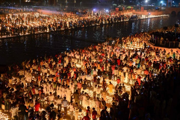 """indu devotees light earthen lamps on the banks of the River Sarayu on the eve of """"Diwali"""" festival during an event organised by the Uttar Pradesh government, in Ayodhya on October 26, 2019. AFP Photo"""
