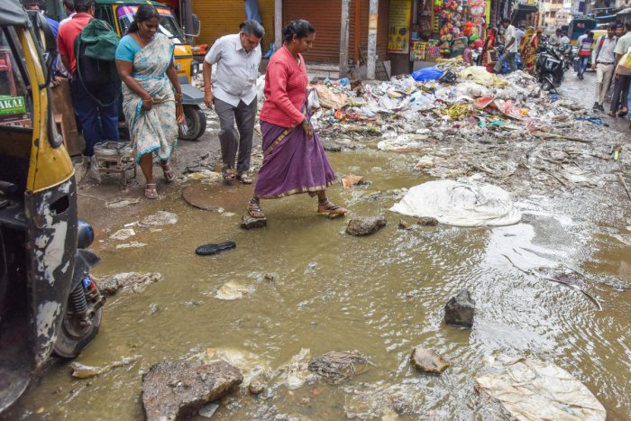 People suffer to cross the road, due to sewage under ground pipe is block from last twenty days and water flowing on the road at Kumbarpet OK road, Avenue road cross in Bengaluru on Friday. DH Photo