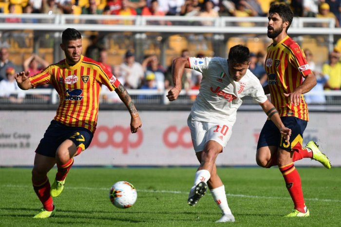 Juventus' Argentine forward Paulo Dybala (C) shoots on goal past Lecce's Italian defender Marco Calderoni (L) during the Italian Serie A footbal match Lecce vs Juventus on October 26, 2019 at the Stadio Comunlae Via del Mare in Lecce. (Photo by Alberto PIZZOLI / AFP)