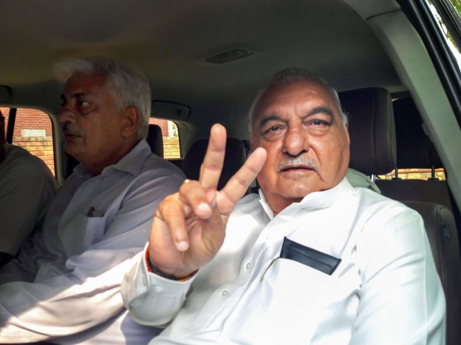Congress veteran leader and former chief minister Bhupinder Singh Hooda flashes the victory sign as he leaves from a counting centre, in Rohtak. (PTI Photo)