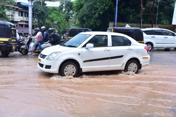Vehicles wade through the rainwater on a road at Bejai in Mangaluru on Saturday.