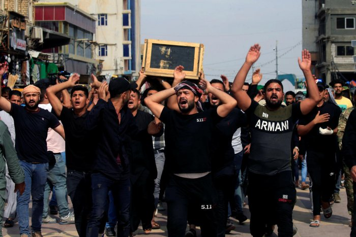 Men react as they carry the coffin of a demonstrator who was killed during anti-government protests, in Najaf, Iraq October 27, 2019. REUTERS/Alaa al-Marjani