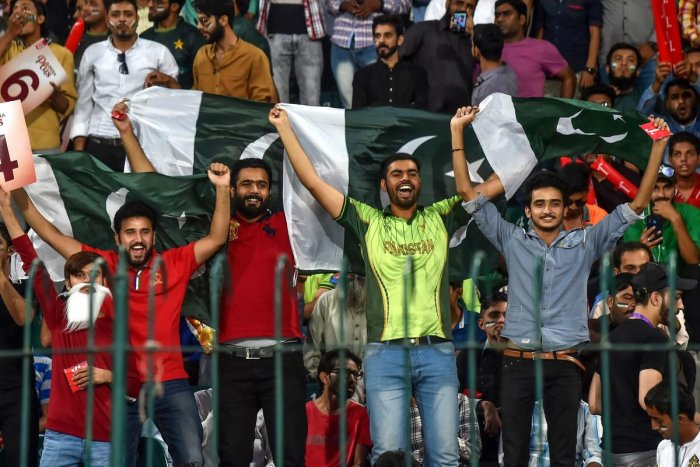 Spectators hold Pakistani flags as they cheer during the third and final Twenty20 International cricket match between Pakistan and Sri Lanka at the Gaddafi Cricket Stadium in Lahore on October 9, 2019. AFP file photo