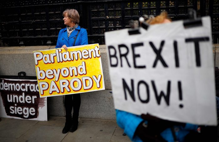 Pro-Brexit activists hold placards as they demonstrate outside the Houses of Parliament in London. (AFP Photo)