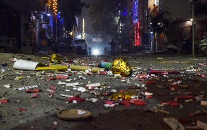A view of a street littered with firecrackers waste during Diwali celebrations, in New Delhi on  Sunday. (PTI Photo)