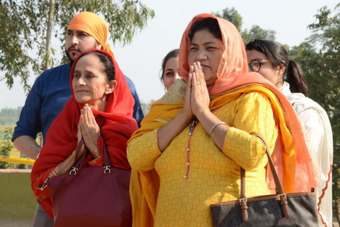 Sikh devotees offers prayers as they look towards the Gurdwara Kartarpur Sahib, which is situated in Pakistan. AFP Photo