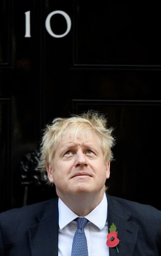 Britain's Prime Minister Boris Johnson reacts as he poses for a photo during a meeting with fundraisers for the Royal British Legion outside Downing Street in London. (Reuters Photo)