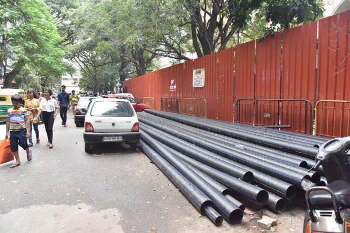 Near Janatha Bazaar in Jayanagar, large metal sheets cut off an entire stretch of footpath, forcing pedestrians to walk on the busy-traffic road. DH Photo by JANARDHAN B K