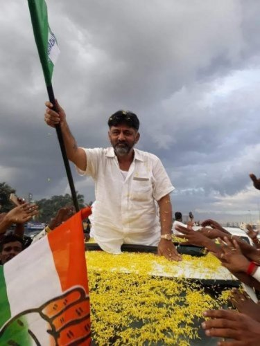 Former Congress minister D K Shivakumr waves JD(S) flag during a rally organised to welcome him on his arrival in Bengaluru, recently.