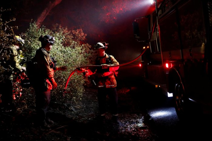 A firefighter passes a hose to douse a hot spot during the Kincade fire in Healdsburg, California. (Reuters Photo)