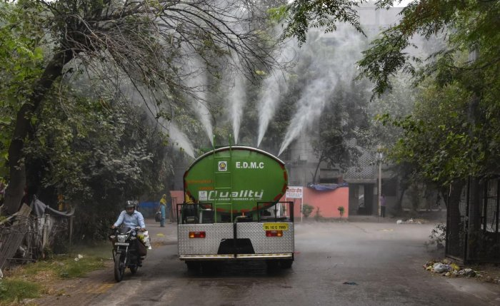 A water tanker sprays water into the atmosphere to curb rising pollution at Gautam Puri in New Delhi, Tuesday, Oct. 29, 2019. (PTI Photo)