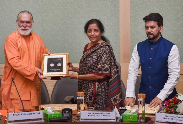 Union Finance Minister Nirmala Sitharaman presents a commemorative coin to Swami Vishwananda Giri on completion of 125th Birth Anniversary of Paramahansa Yogananda, in the presence of MoS Finance Anurag Thakur, in New Delhi on Tuesday. (PTI Photo)