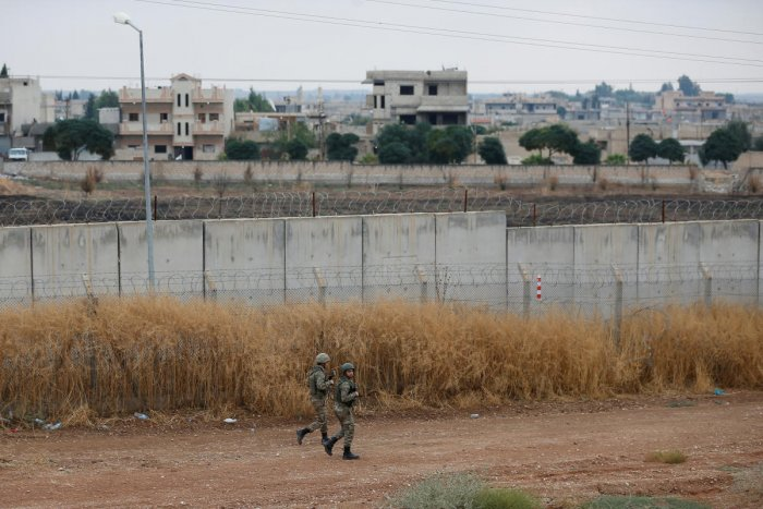 Turkish soldiers patrol along a wall on the border line between Turkey and Syria (Photo by Reuters)