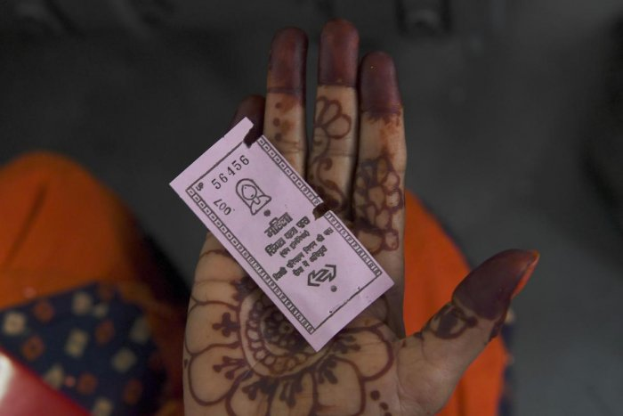 woman travelling on a Delhi Transport Corporation bus shows a pink ticket in New Delhi on October 29, 2019, allowing her to a free ride following a Delhi goverment travel scheme distributing free bus tickets for women safety and empowerment. (AFP)
