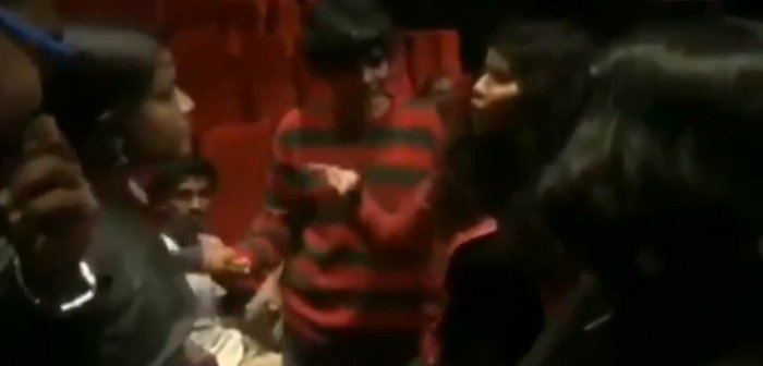 A screengrab from the video that shows a crowd of people heckling a group at a theatre for not standing for the National Anthem.