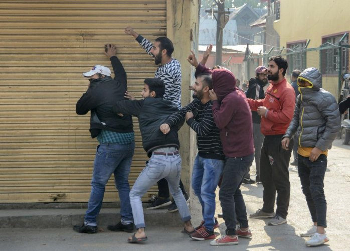 Youth throw stones towards security personnel during a protest in Srinagar. (PTI Photo)